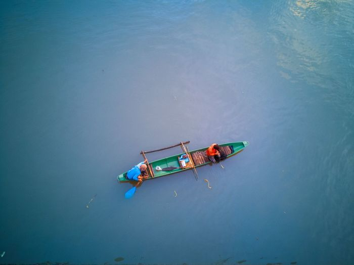 High Angle View Of Fishermen In Boat Floating On Sea