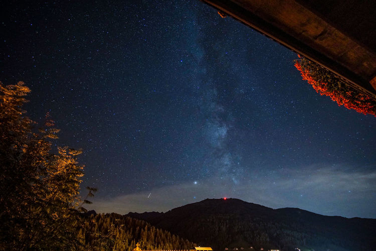 Scenic view of mountains against sky with milky way at night