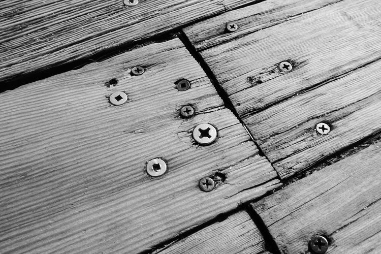 Close-up of screws fixed on wooden planks