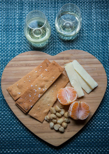 Heart cutting board with cheese and crackers Tangerine Appetizer Food Cracker Overhead Macadamia Fruit Snack Heart Platter Cheese Wine