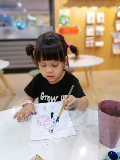 Girl painting on paper at table in classroom