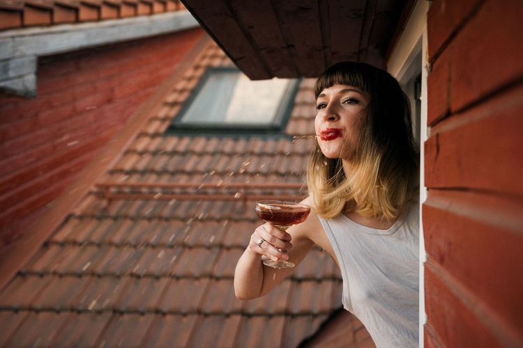 Young woman spitting red wine while sitting on window in house