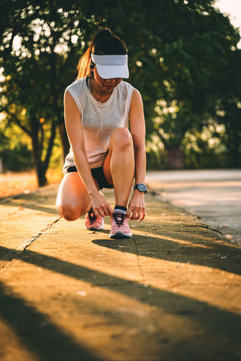 Woman runner does jogging on the city road. Sport and workout. Sport Workout Jogging Running Exercise Sunlight One Person Sitting Real People Shadow Full Length Leisure Activity Nature Lifestyles Day Young Adult Tree Women Casual Clothing Plant Young Women Outdoors Adult Hairstyle Shorts