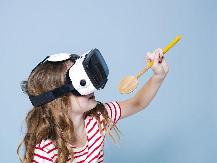 cool and smiling positive girl wearing virtual reality glasses goggles headset is singing with cooking spoon, new generation, concept in front of blue background Childhood Child Holding Studio Shot Girls Leisure Activity Women Indoors  Females People Blue Headshot Portrait Hair Copy Space Lifestyles Striped Hairstyle Blue Background Innocence 3D Virtual Cooking Spoon Goggles Girl