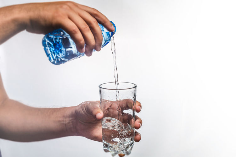 Midsection of person pouring drink in glass against white background