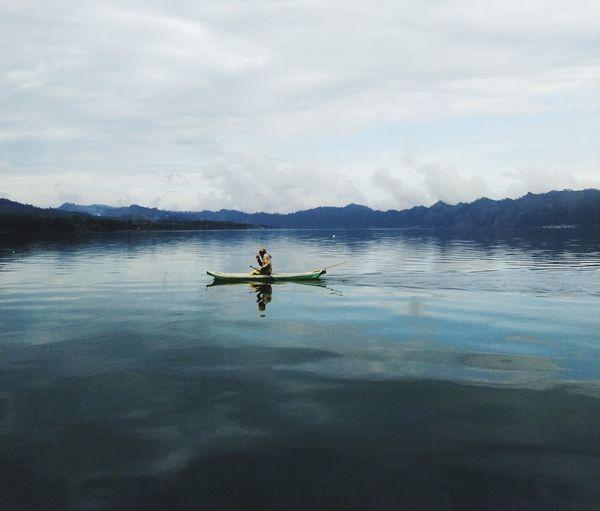 Men on boat in lake against sky