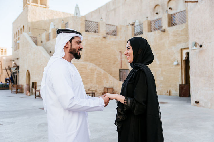 Side view of romantic couple holding hands while standing in town