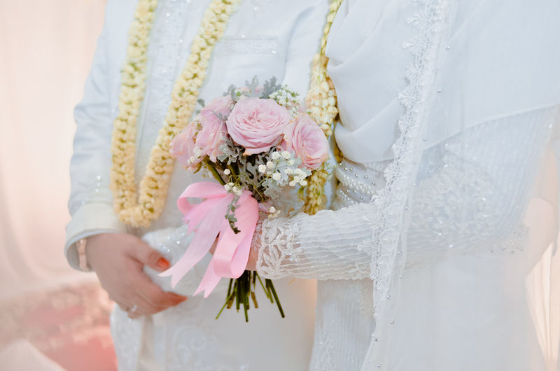 Midsection of wedding bride standing with bouquet of flowers