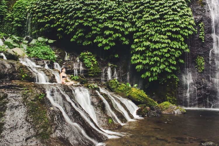 Woman In Lotus Position Doing Yoga At Waterfall