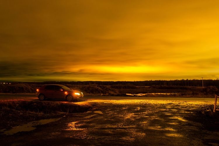 Car on illuminated road against sky during sunset