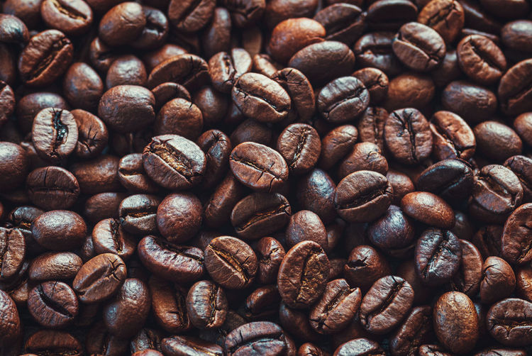 Coffee beans background, dark and light brown roasted coffee-beans closeup