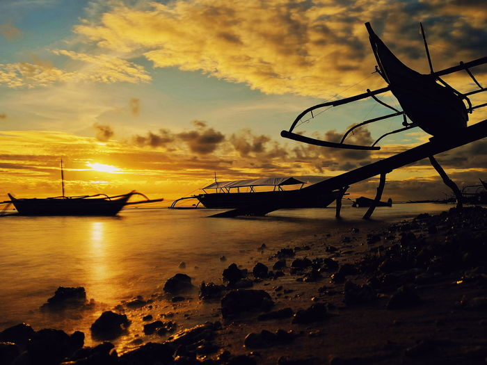 Silhouette boats moored on beach against sky during sunset