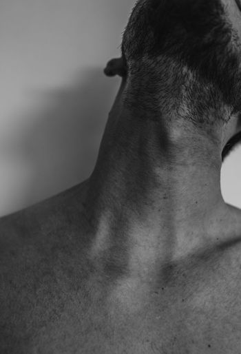 Close-up of shirtless man against gray background