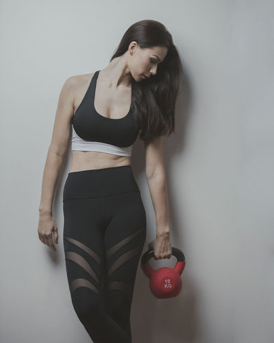 Long haired beautiful fitness model athlete poses against a gray wall holding a red kettle bell while wearing a tight sports outfit Body & Fitness Dance Exercising Silhouettes Stretching Legs Workout Flow Yoga Pose Abdominal Muscles Art Background Exercise Ball Fitness Outfit Kettle Bell Long Hair Pilates Pilateslovers Pink Color Pose Pretty Girl Rubber Band Sports Clothing Studio Shot