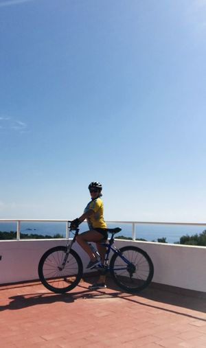 Man riding bicycle against clear blue sky
