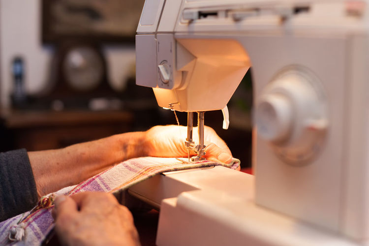 Cropped hands of woman using sewing machine at workshop