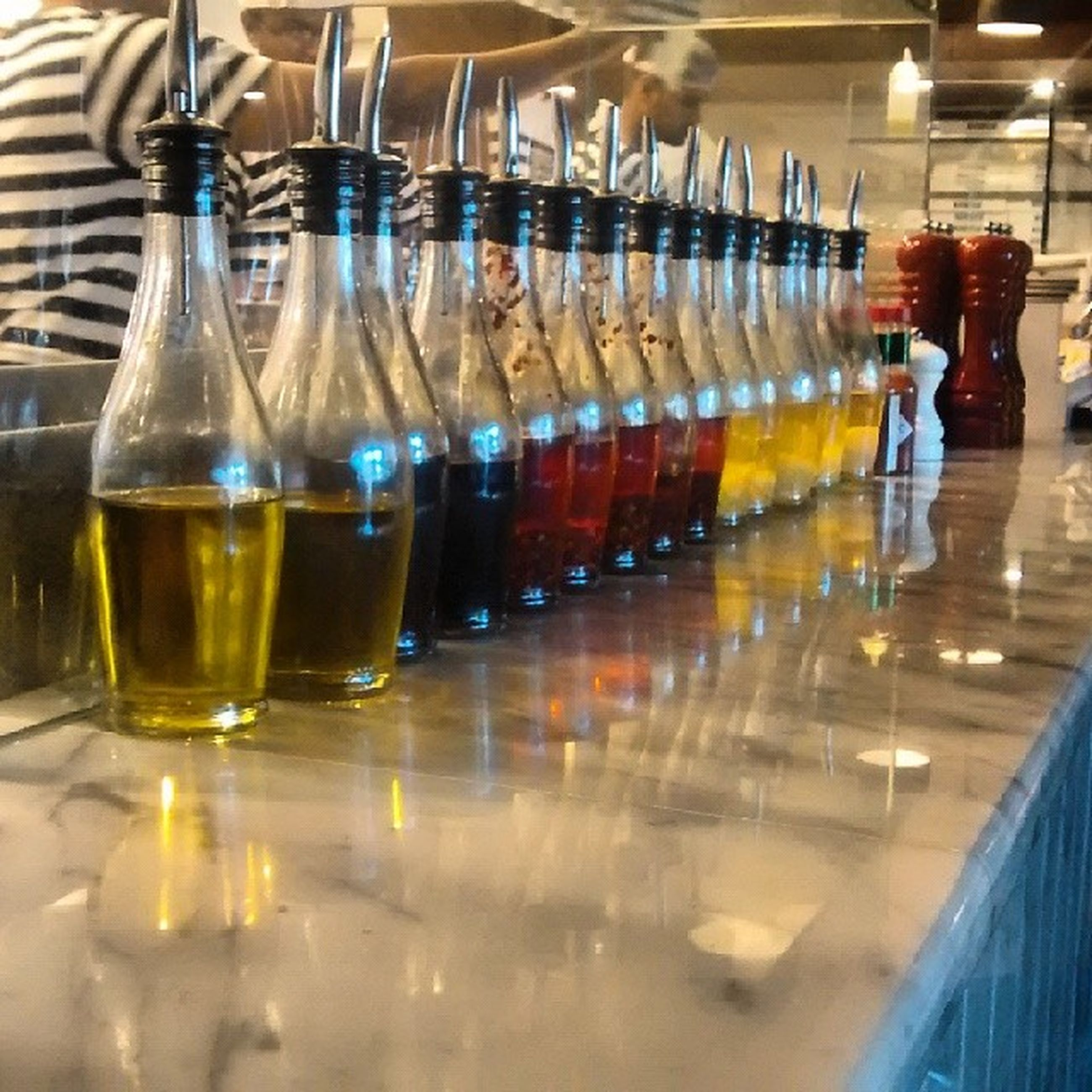 indoors, drinking glass, drink, table, food and drink, refreshment, glass - material, still life, alcohol, restaurant, wineglass, transparent, bottle, glass, reflection, empty, wine, in a row, close-up, arrangement