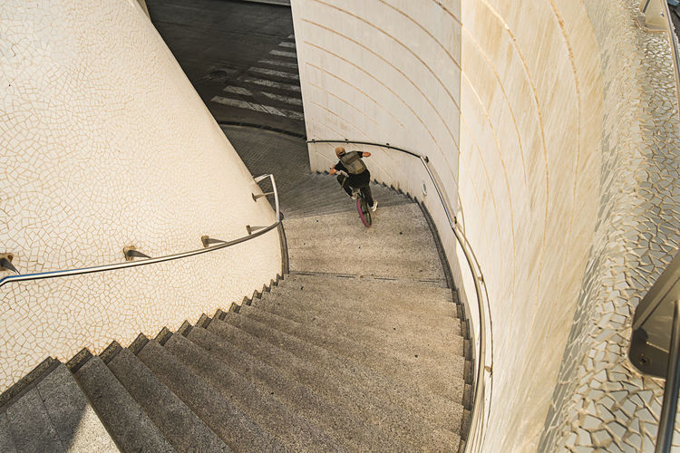 Rear view of man walking on staircase