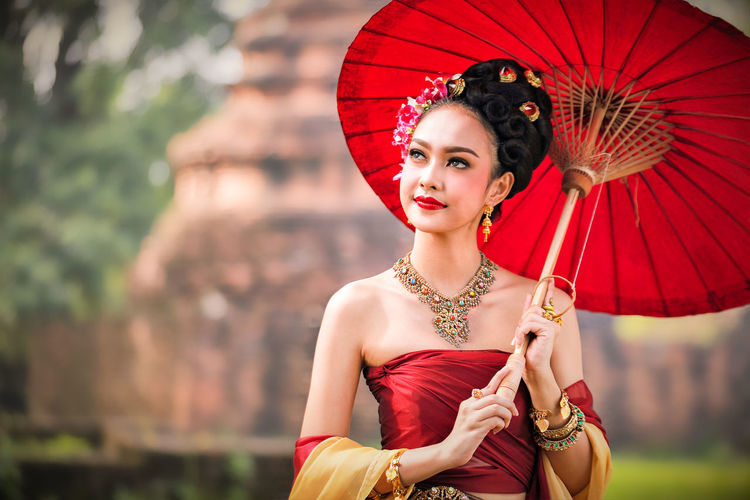 Beautiful young woman wearing traditional clothing while holding umbrella