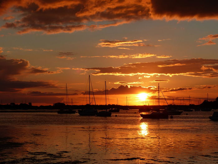Silhouette sailboats moored on sea against sky during sunset