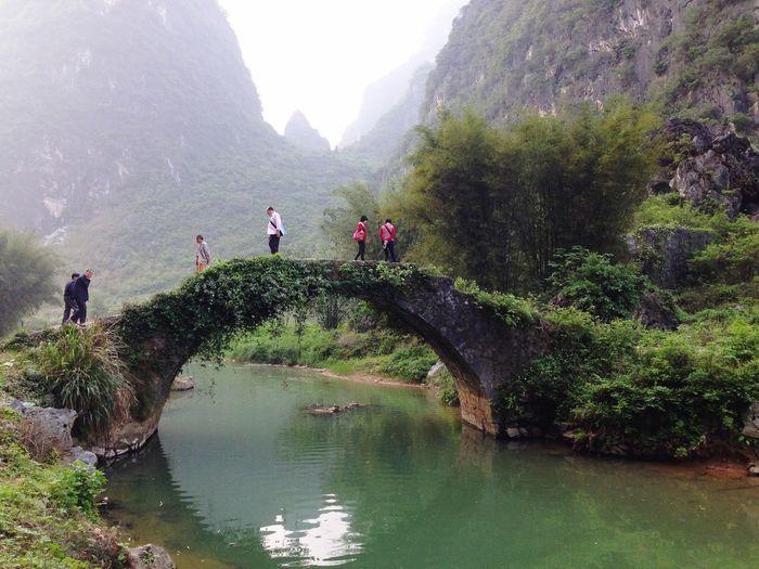 Group of people walking on footbridge over lake