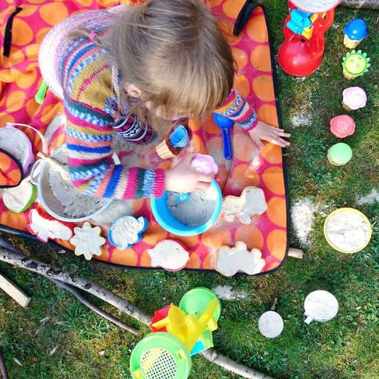 High angle view of girl playing with toy toys