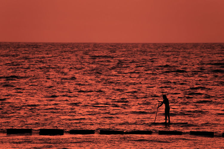 Silhouette person standing on sea against sunset sky