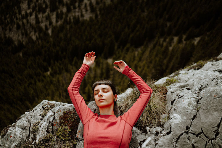 Portrait of woman with arms raised on mountain