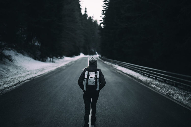 Rear view of woman with backpack walking on road during winter