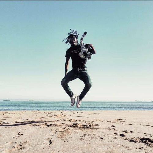 Full length of man jumping on shore at beach against blue sky