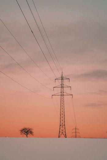 Electricity pylon against romantic sky at sunset