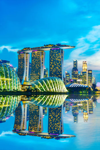 Singapore Skylines downtown and Financial District buildings reflection along at twilight time Marina Bay Sands Singapore Twilight Architecture Bay Blue Building Building Exterior Built Structure City Cityscape Cloud - Sky Financial District  Hotel Luxury Modern No People Office Building Exterior Outdoors Reflection Sky Skyscraper Travel Destinations Water Waterfront