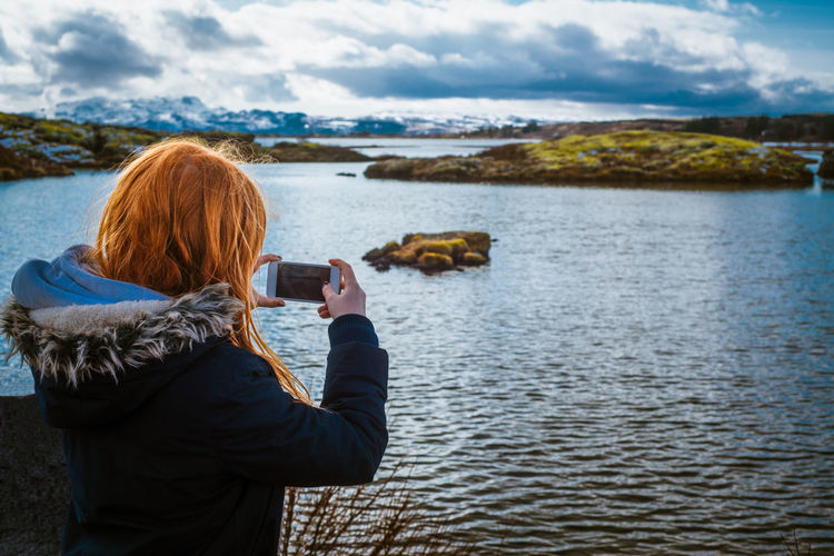 Rear view of girl photographing sea during winter