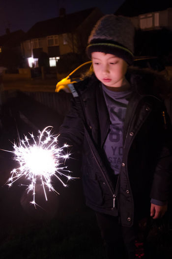 A young boy playing with a sparkler. Bonfire Night Boy Childhood Childhood Memories Dark Fireworks Night. No People. Fun Guy Fawkes Night Happiness Happy Low Light Night Nighttime One Person Outdoors Outside Spa Sparkler Sparks Young Young Adult