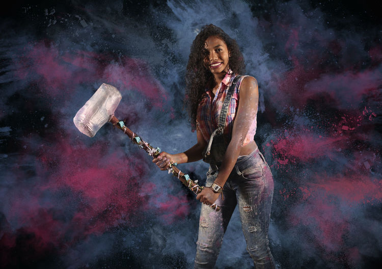 Portrait Of Young Woman Holding Hammer While Standing Against Colored Background