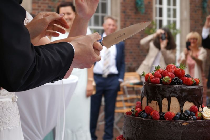 """The """"fight"""" who will have the hand above the other hand... will be the boss... Cropped Female Male Hands Holding Knife Wedding Cake Chocolate Cakes Groom Bride Happy Day Macro Photography Cropped People Cutting Cake Suit Strawberries Coffee Time Sweet Food Coffee Guests People In The Background German Tradition Berries The Photojournalist - 2016 EyeEm Awards EndlessLove Summer Wedding"""