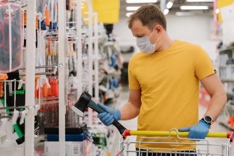 Man wearing mask while shopping in supermarket