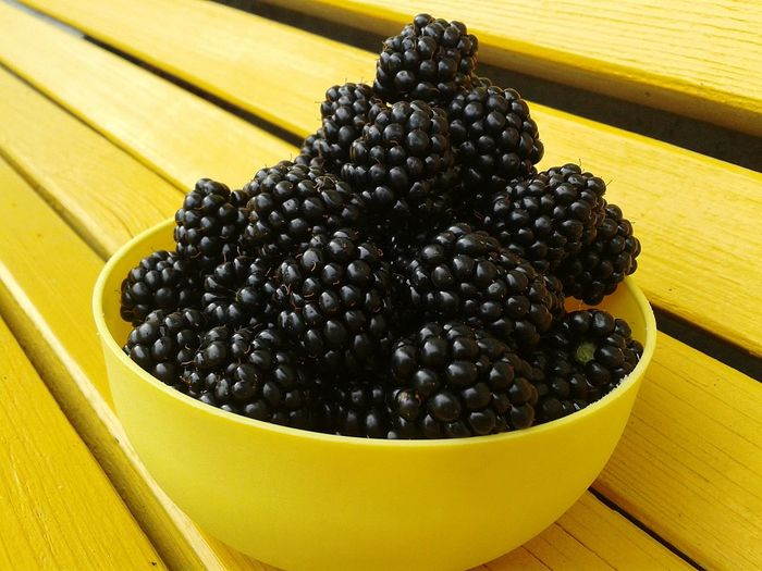 Close-Up Of Blackberry Fruits In Bowl On Yellow Bench