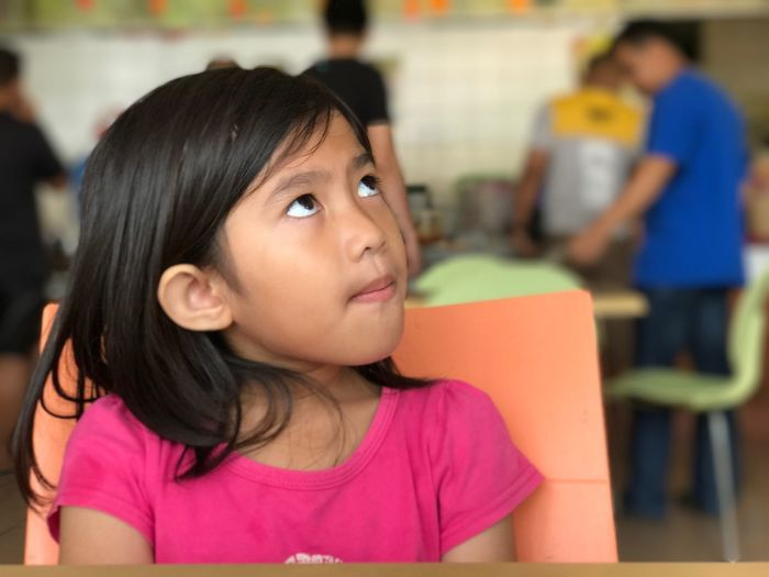 Girl Sitting On Chair In Classroom