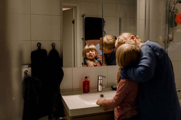 Rear view of people in bathroom