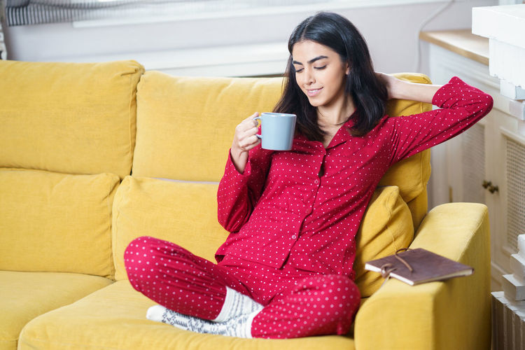 Young woman sitting on sofa at home