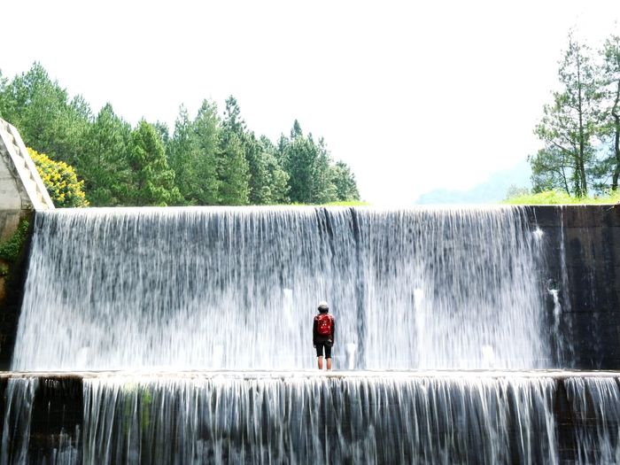 Man standing by waterfall against sky