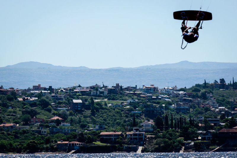 Kitesurfers over lake on sunny day