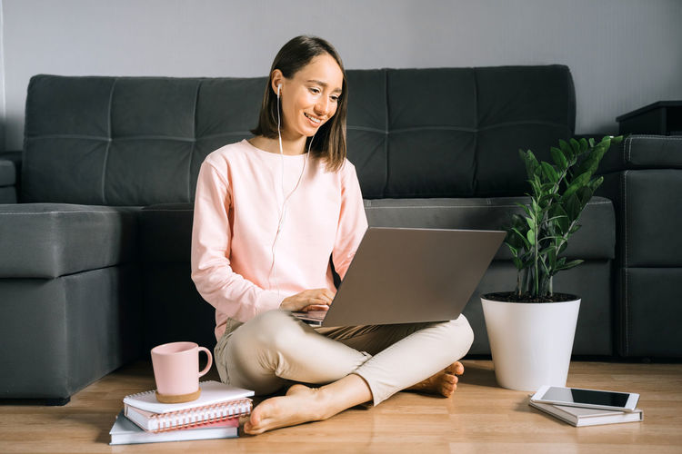 Young woman sitting on the floor near couch and using laptop, calling by video. working from home.