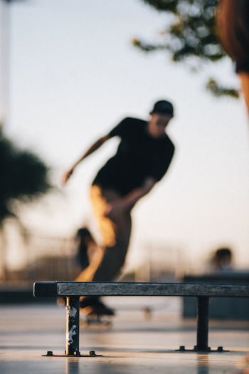 Man Skateboarding At Skateboard Park With Bench In Foreground