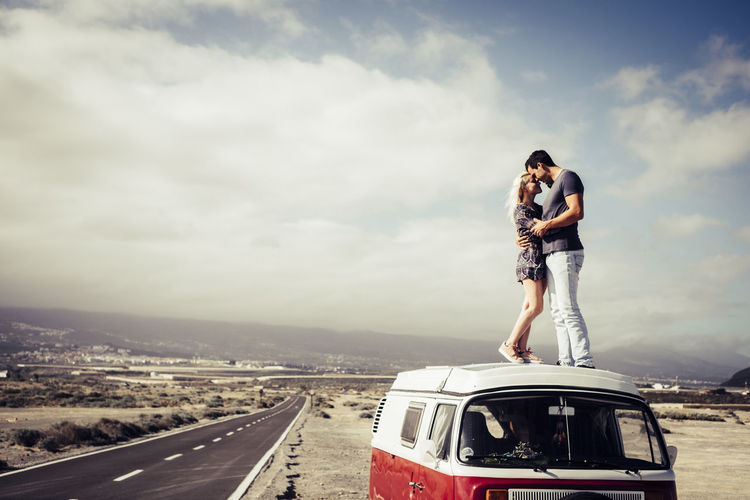 Couple standing on camper trailer at desert against cloudy sky