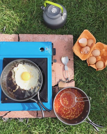 Directly above shot of breakfast with camping stove on grassy field
