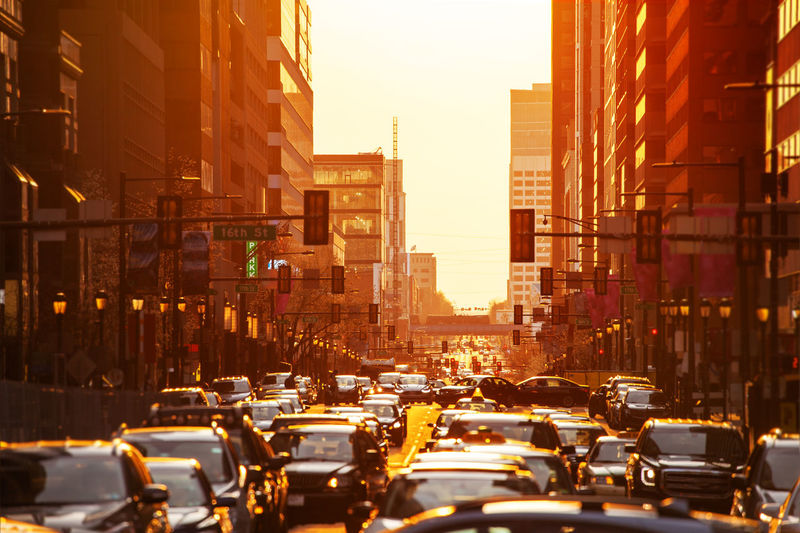 Cars on street amidst buildings in city during sunset