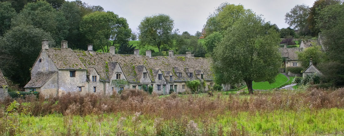 """Arlington Row, Bibury This is the picturesque Arlington Row in Bibury ,Gloucester an iconic English artist and craftsman William Morris called Bibury """"the most beautiful village in England"""". Built around 1280 as a monastic wool store, the building was converted in the seventeenth century into a row of cottages for weavers. Arlington Row, Cotswolds Architecture Bibury Building Building Exterior Built Structure Grass Green Color History House Land Nature The Past Tranquil Scene Tree"""