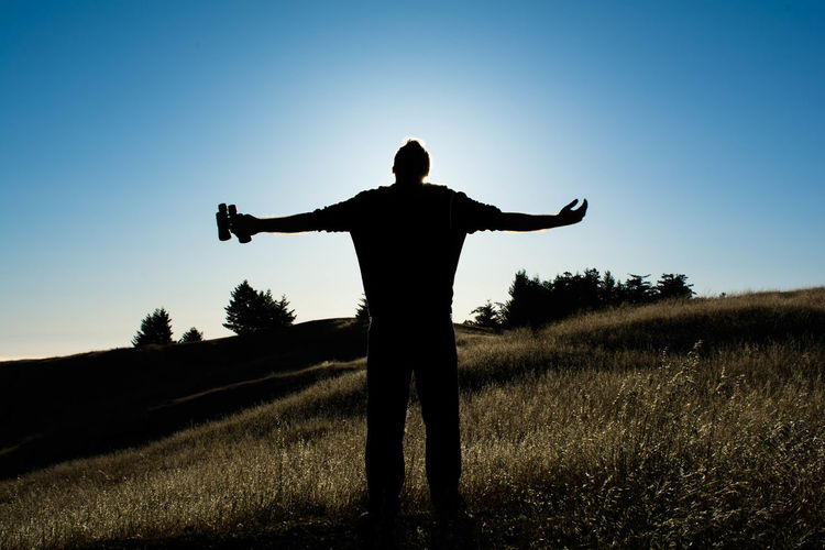 Silhouette man with arms outstretched standing on grassy field against sky